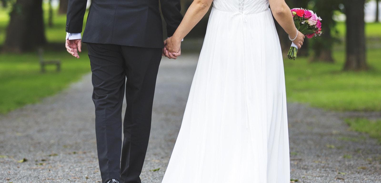 man and woman in wedding attire walking down sidewalk holding hands