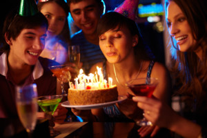 Men and women clebrating a birthday with candles on a cake and adult beverages